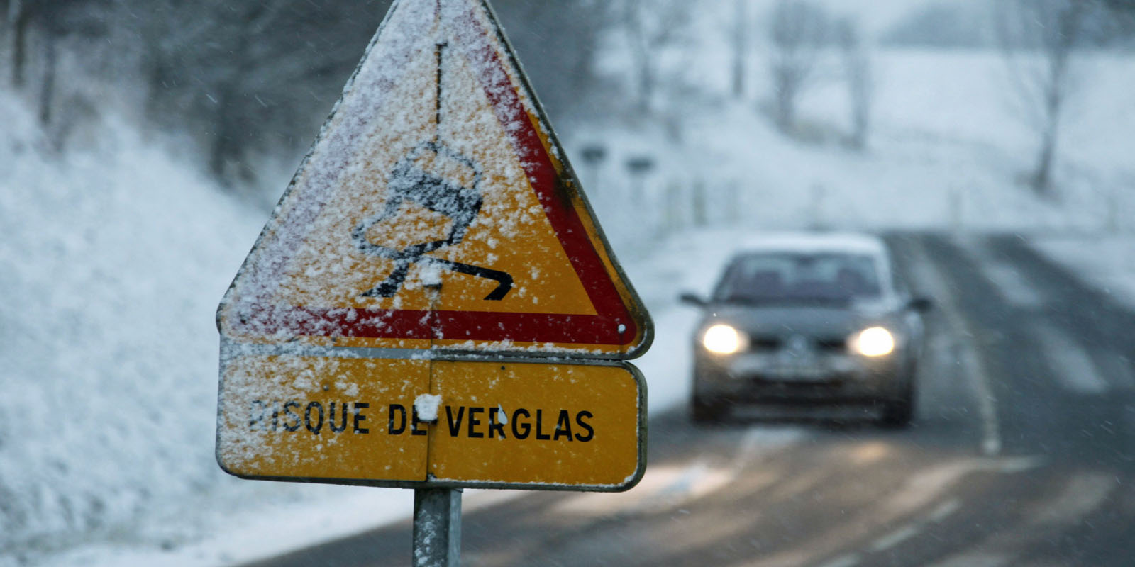 A car drives on a snow-covered road in Quievy near Cambrai, northern France, as winter weather hits France January 5, 2009. REUTERS/Pascal Rossignol (FRANCE)